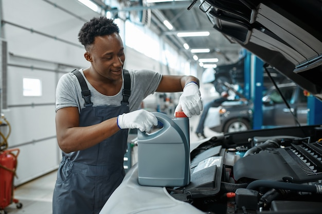 Man werknemer verandert olie in motor in mechanische werkplaats
