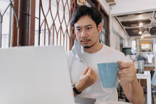 Man werkt in café met masker op het gezichtsconcept freelance met covid