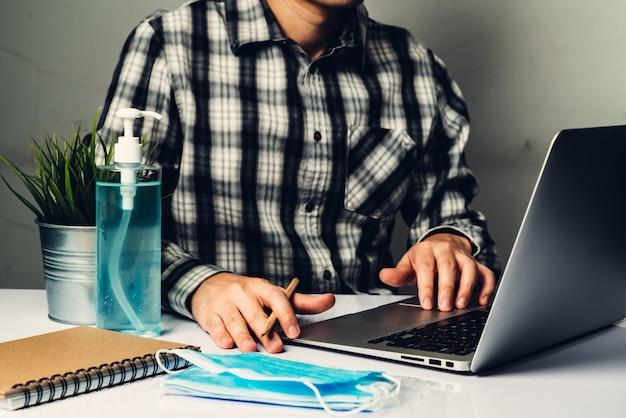 Man werkt op kantoor thuis om te beschermen tegen de ziekte van coronavirus of covid-19.