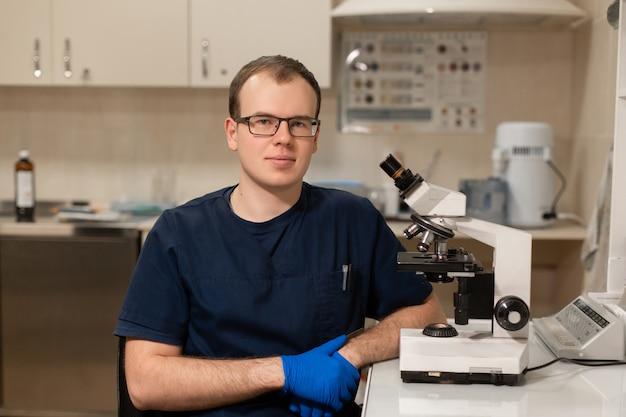 Man wetenschapper, medisch werker, tech of afgestudeerde student werkt in modern biologisch laboratorium