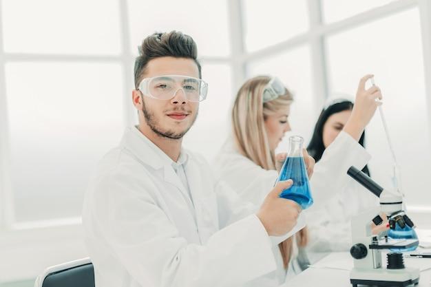 Man wetenschapper met een kolf met vloeistof voor het experiment