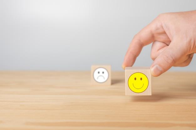 Man wijst met zijn vinger naar houten kubus met positieve gezichtskubus met teken negatief gezichtspictogram is wazig
