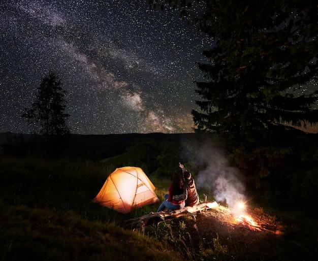 Man wijst naar de ongelooflijk mooie sterrenhemel en de melkweg. paarzitting dichtbij de gloeiende tent, de bomen en het vuur bij login bergen. romantisch kamperen in de avond onder de fantastische sterrenhemel