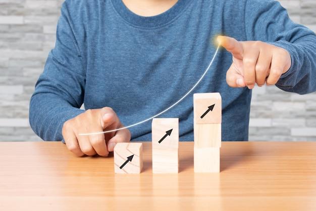 Man wijst naar groei en vermeerdert met houten kubus die als traptrede wordt gestapeld. business concept groei succes proces.