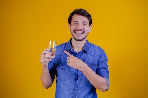 Man wijst naar het glas water in zijn hand op gele achtergrond. gezondheid en medisch concept