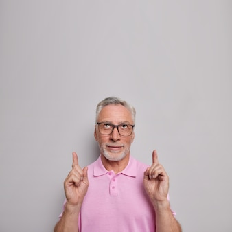 Man wijst wijsvinger op hoofd geeft advies wat te kiezen demonstreert enthousiaste promo draagt transparante bril casual t-shirt introduceert online winkel promo