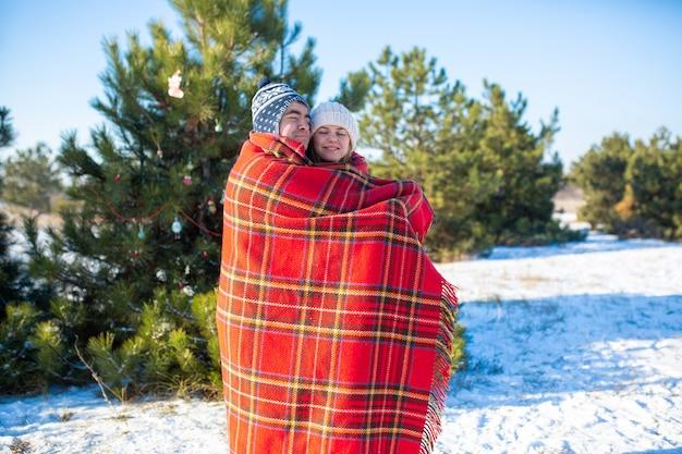 Man wikkelt zijn vriendin in een warme rode geruite plaid zodat ze zichzelf verwarmt
