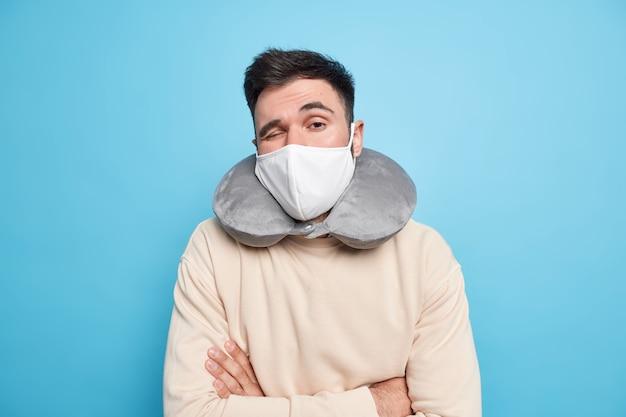 Man wil rust hebben houdt armen gevouwen draagt beschermend masker tijdens pandemie van coronavirus opgeblazen nekkussen poseert in casual trui