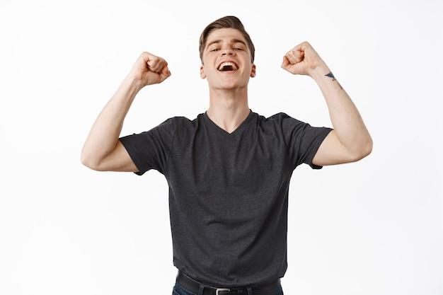 Man winnen weddenschap, zingen en kijken met een blij gezicht, handen opsteken en ja schreeuwen met tevredenheid, triomferen.