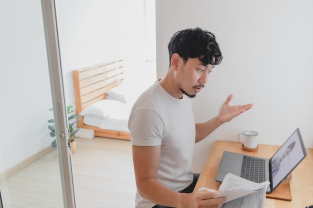 Man woont een vergaderconferentie bij met zijn collega terwijl hij thuis werkt