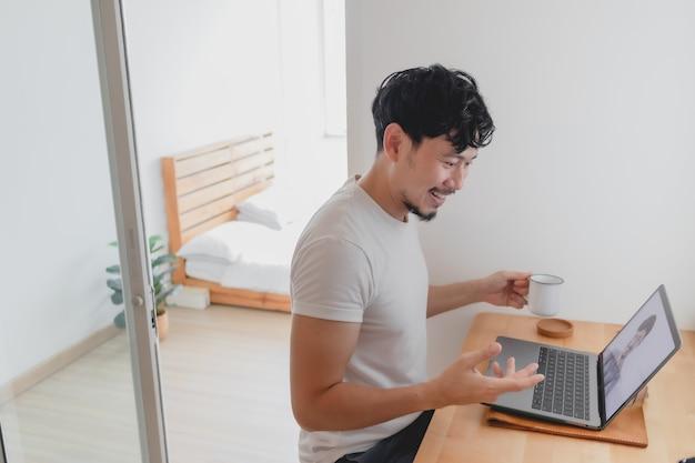 Man woont een vergadering bij met zijn collega terwijl hij thuis werkt