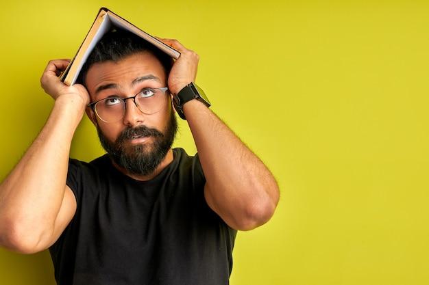 Man wordt gek, moe van onderwijs. gemengd ras arabische man in bril met boek op hoofd, opzoeken, geïsoleerde groene achtergrond