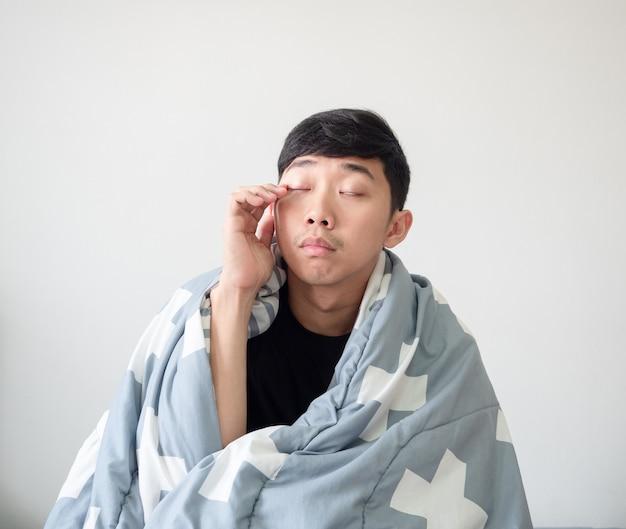 Man wordt wakker met de deken, bedek zijn lichaam, raak oog met de hand aan en voel zich slaperig slaperig man-concept