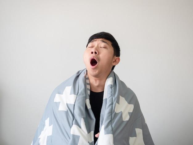 Man wordt wakker met een deken die zijn lichaam bedekt en voelt zich slaperig en geeuw sluit het oog op wit geïsoleerd