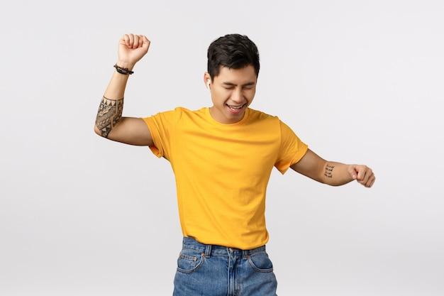 Man wordt wild, heeft plezier en geniet van het leven. aantrekkelijke aziatische hipster man in geel t-shirt, getatoeëerd, handen omhoog en zorgeloos dansen als luisteren muziek draadloze hoofdtelefoons, witte muur