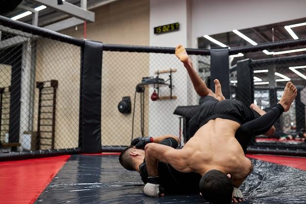 Man worstelaars van worstelen maakt onderwerping worstelen. oefen vechttechnieken, vechten op de vloer in de sportschool, samen trainen, trainen