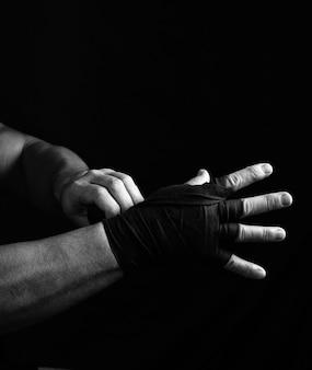 Man wraps zijn handen in zwarte textiel bandage voor sport