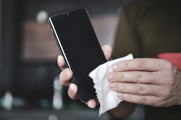 Man wrijft met een doek over het scherm van zijn zwarte smartphone. preventie van coronavirus en virale ziekten. de mobiele telefoon stofvrij maken.