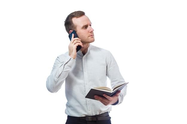 Man zakenman, leraar, mentor onderzoekt vermeldingen in uw dagboek en praten op een mobiele telefoon. geïsoleerd op witte achtergrond