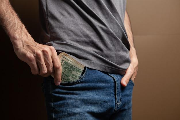 Man zet geldzak op bruine achtergrond