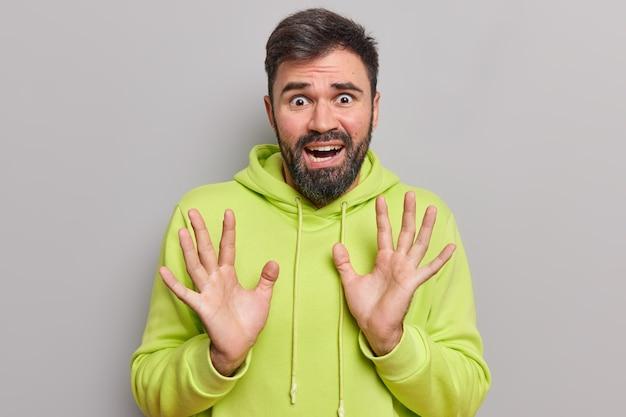 Man ziet er bang uit heeft fobieën verhoogt handpalm probeert zichzelf te beschermen tegen iets vreselijks draagt casual hoodie ziet er wanhopig en verwoest uit geïsoleerd op grijs