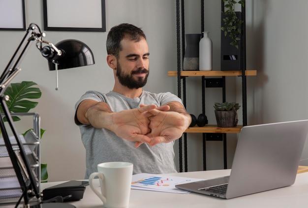 Man zijn armen strekken tijdens het werken vanuit huis