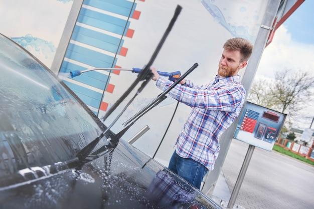 Man zijn auto schoonmaken in een zelfbediening