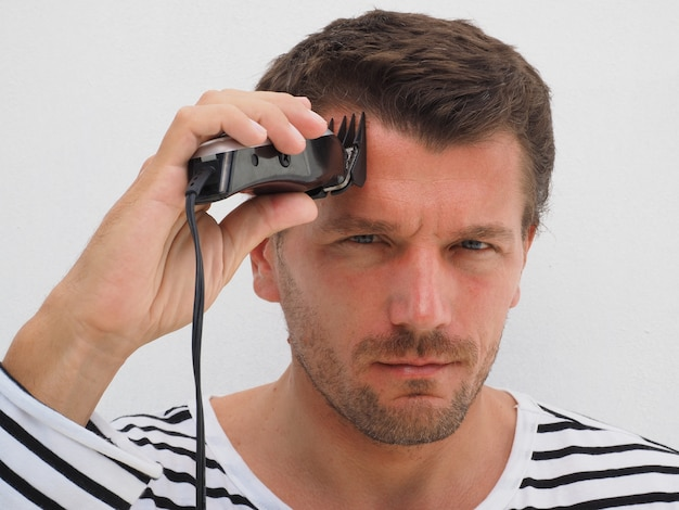 Man zijn eigen haar knippen met een tondeuse. levensstijl.
