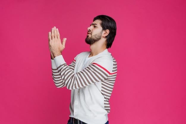 Man zijn handen verenigen en bidden.