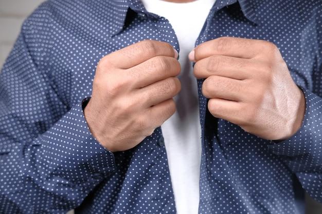 Man zijn overhemd dichtknopen