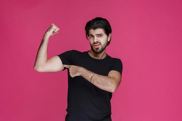 Man zijn vuist en spieren demonstreren als bokser of sportman.