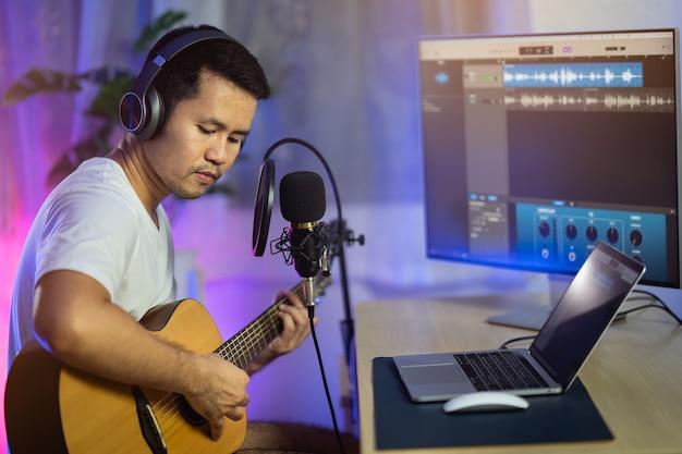 Man zingt met hoofdtelefoon en speelt gitaar die nieuw nummer opneemt met microfoon in de thuisopnamestudio