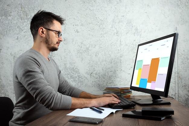 Man zit aan een tafel op kantoor, werkt op een computer.