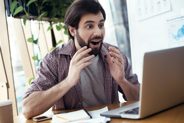 Man zit aan tafel op creatief stijlvol kantoor en kijkt naar l