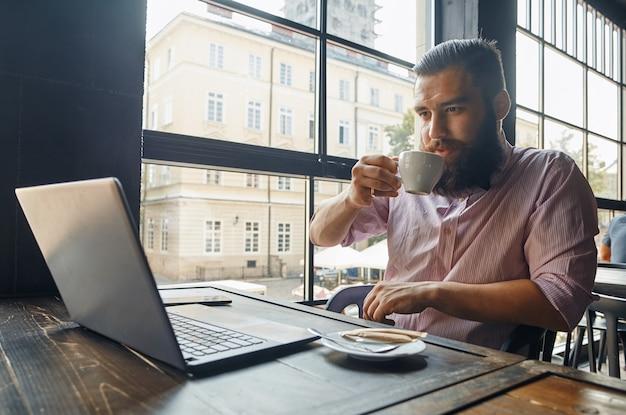 Man zit achter de computer en koffie drinken