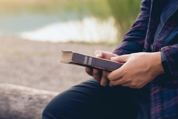 Man zit en houdt de bijbel in zijn handen met de achtergrond van de natuur. zondaglezingen, bijbel