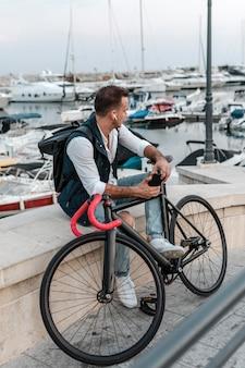 Man zit en kijkt weg naast zijn fiets