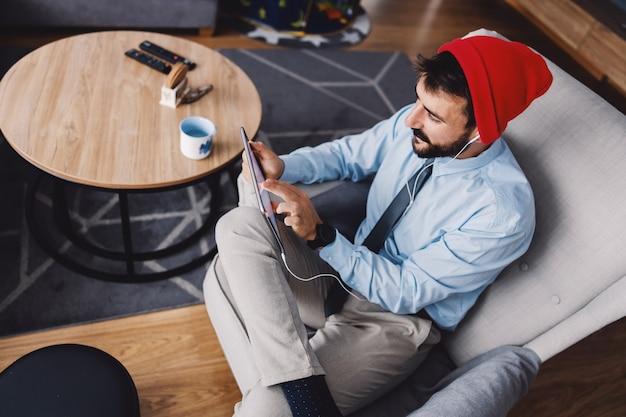 Man zit in de woonkamer en tablet gebruikt tijdens quarantaine. covid-uitbraak concept.