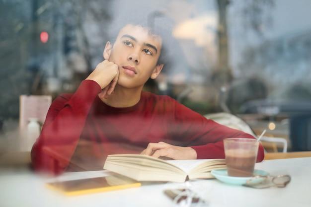 Man zit in een bar, leest een boek en drinkt choccolate