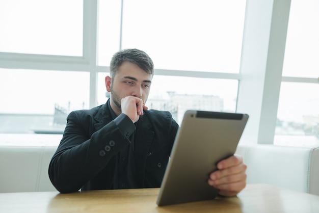 Man zit in een modern café bij het raam en kijkt naar zijn gadget. een zakenman gebruikt een tablet in een restaurant.
