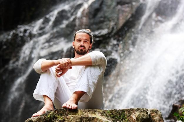 Man zit in meditatie yoga op rots bij waterval in tropisch regenwoud