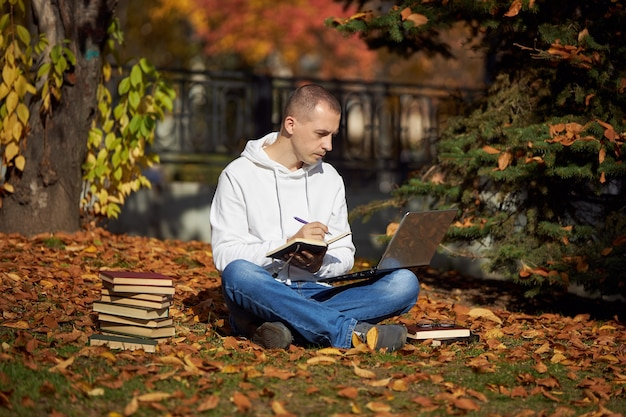 Man zit in park met laptop en leerboeken