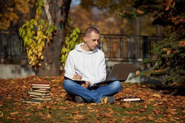Man zit in park met laptop klad blok boeken en leerboeken outdoor learning social distancing