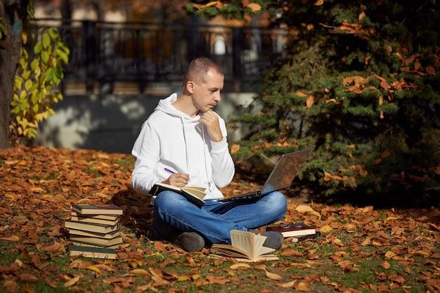 Man zit in park met laptop, kladblok, boeken en leerboeken. buiten leren, sociaal afstand nemen