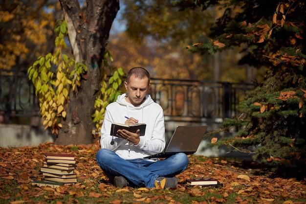 Man zit in park met laptop, kladblok, boeken en studieboeken. buiten leren, social distancing