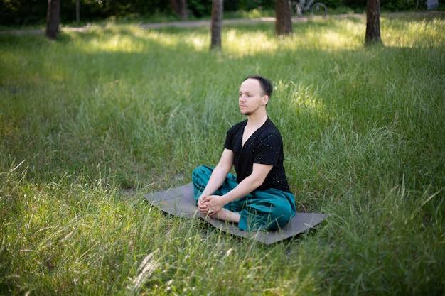 Man zit lotuspositie beoefenen van yoga in het park op groen gras