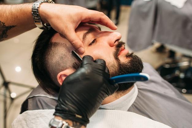 Man zit met gesloten ogen terwijl de kapper hem scheert met een scheermes