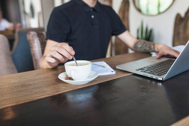 Man zit met laptop en koffie aan tafel