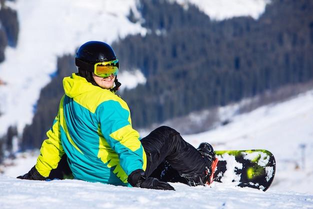Man zit met snowboard op de top van de heuvel met prachtig uitzicht. ruimte kopiëren. zonnige dag