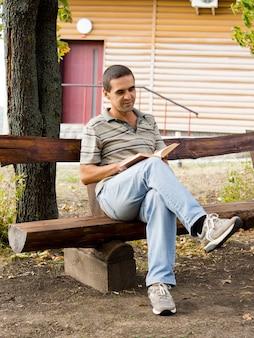 Man zit ontspannen het lezen van een boek op een rustieke houten bank voor een houten blokhut